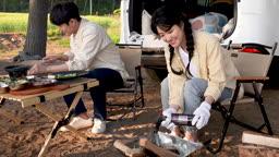 차박캠핑 요리 재료 다듬는 젊은남자와 토치로 장작에 불 붙이는 젊은여자 모습