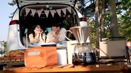 차박캠핑 차 안에 엎드려 풍경 바라보며 대화나누는 젊은남자와 젊은여자 모습