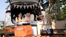 차박캠핑 차 안에 엎드려 대화나누는 젊은남자와 젊은여자 모습