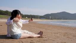 커플 해변가에 앉아 스마트폰으로 사진 셀카 촬영하는 젊은남자와 젊은여자 모습