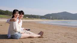 커플 해변가에 앉아 웃는 젊은남자와 젊은여자 모습