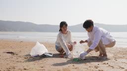 커플 해변가에 버려진 쓰레기를 주워 봉투에 담는 젊은남자와 젊은여자 모습