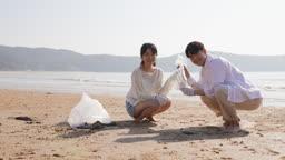 커플 해변가에서 쓰레기봉투 들고 있는 젊은남자와 젊은여자 모습