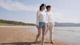 커플 손잡고 해변가를 걷는 젊은남자와 젊은여자 모습