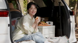 차박캠핑 차 안에 앉아 빵과 커피를 들고 웃는 젊은여자 모습