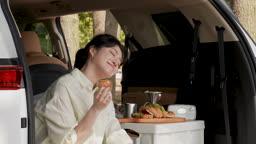 차박캠핑 차 안에 앉아 빵과 머그컵을 들고 있는 젊은여자 모습