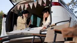 차박캠핑 차 안에서 보드게임하는 젊은남자와 젊은여자 모습