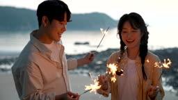 커플 스파클러 들고 불꽃놀이하는 젊은남자와 젊은여자 모습