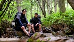 백팩킹 계곡 바위에 앉아 휴식을 취하다 카메라 응시하며 미소짓는 젊은남자 모습