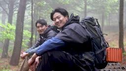 백팩킹 등산하다 앉아 휴식을 취하며 카메라 응시하며 미소짓는 젊은남자 모습