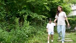 교감 가족 잔디 밭 위 나무 길을 걸어가는 엄마와 딸 모습