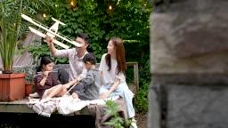 교감 가족 평상에 앉아 나무 비행기 모형 가지고 노는 가족 모습