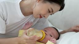 가족 누워있는 아기와 분유를 먹여주는 젊은엄마 모습