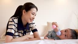 가족 엎드려 서로 마주보며 딸랑이로 노는 젊은엄마와 아기 모습