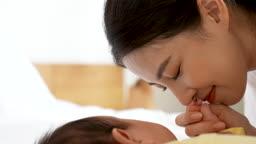 가족 자는 아기의 손을 잡고 미소짓고 있는 젊은엄마 모습