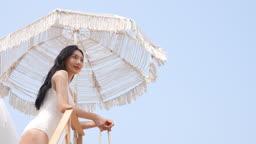 비키니 수영복 입고 파라솔 아래에서 포즈를 먼 곳을 바라보는 젊은여자 모습
