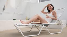 비키니 수영복 입고 썬베드에 앉아 샴페인 마시는 젊은여자 모습