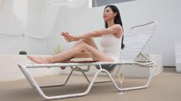 비키니 수영복 입고 썬베드에 앉아 스트레칭하며 포즈 취하는 젊은여자 모습