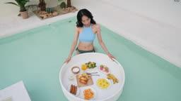 비키니 수영복 입고 플로팅 식사를 즐기는 젊은여자 모습