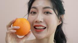 오렌지 들고 카메라 응시하며 포즈 취하는 젊은여자 모습