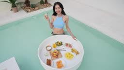 비키니 수영복 입고 카메라 응시하며 플로팅 식사를 즐기는 젊은여자 모습