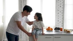 가족 아일랜드 식탁에 앉아 미소 지으며 대화 나누는 아빠와 딸 모습