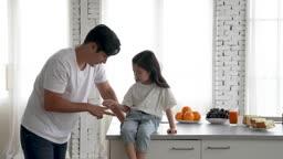 가족 아일랜드 식탁에 앉아 가위바위보 게임하며 미소 짓는 아빠와 딸 모습