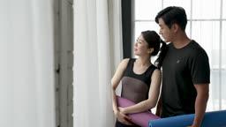 부부 집 창가에서 홈트레이닝 후 운동 매트 들고 쉬며 대화하는 부부 모습