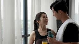 부부 집 창가에서 홈트레이닝 후 음료 들고 쉬며 대화하는 부부 모습