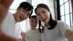 가족 미소 지으며 영상통화하는 가족 모습