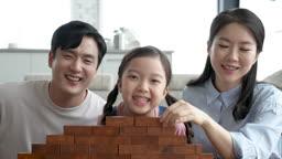 가족 즐겁게 블록놀이 미소 지으며 카메라 응시하는 가족 모습