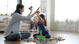 가족 즐겁게 블록놀이 미소 지으며 하이파이브 하며 카메라 응시하는 가족 모습