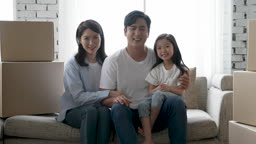 가족 집 이사준비 소파에 앉아 미소 지으며 카메라 응시하는 가족 모습