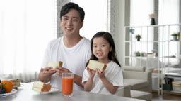 가족 집 아침 브런치 샌드위치 들고 미소 지으며 카메라 응시하는 아빠와 딸 모습