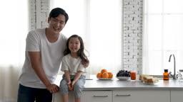 가족 아일랜드 식탁에 앉아 미소 지으며 카메라 응시하는 아빠와 딸 모습
