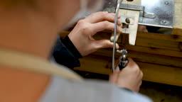 반지공방 반지 제조 과정 모습 작업실에서 반지 재료를 톱질하는 손 모습
