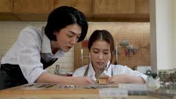 반지공방 반지 제조 과정 모습 작업실에서 톱질을 하며 제조 방법을 알려주는 젊은남자와 젊은여자 모습