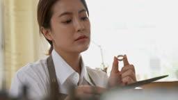 반지공방 반지 제조 과정 모습 작업실에서 완성된 반지를 돌려보며 보는 젊은여자 모습
