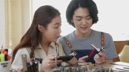 반지공방 반지 제조 과정 모습 반지 재료에 망치로 두드리며 다듬는 젊은남자와 사진을 찍어주는 젊은여자 모습